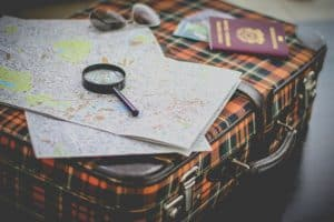 Maps, passport, and magnifying glass on suitcase