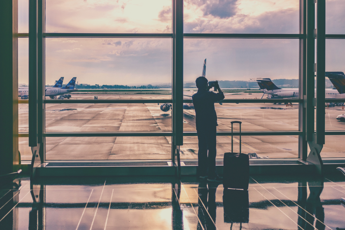 man in airport taking photo of planes