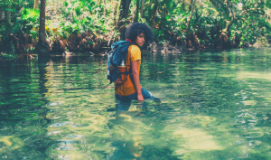 Person walking through water with backpack