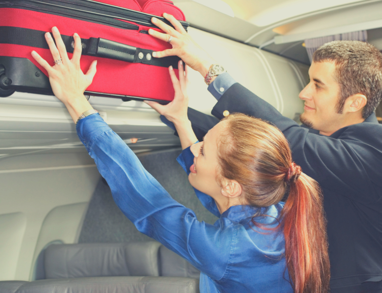 Woman and man with suitcase in airplane