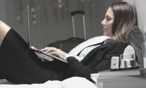 Woman working with laptop on hotel bed