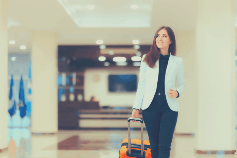 Woman walking in hotel with suitcase