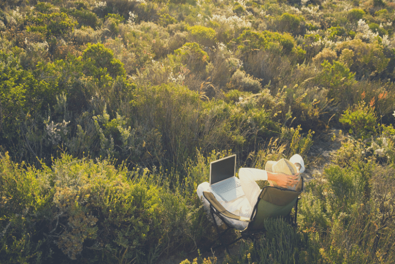 Person relaxing with laptop outdoors - mancro backpacks