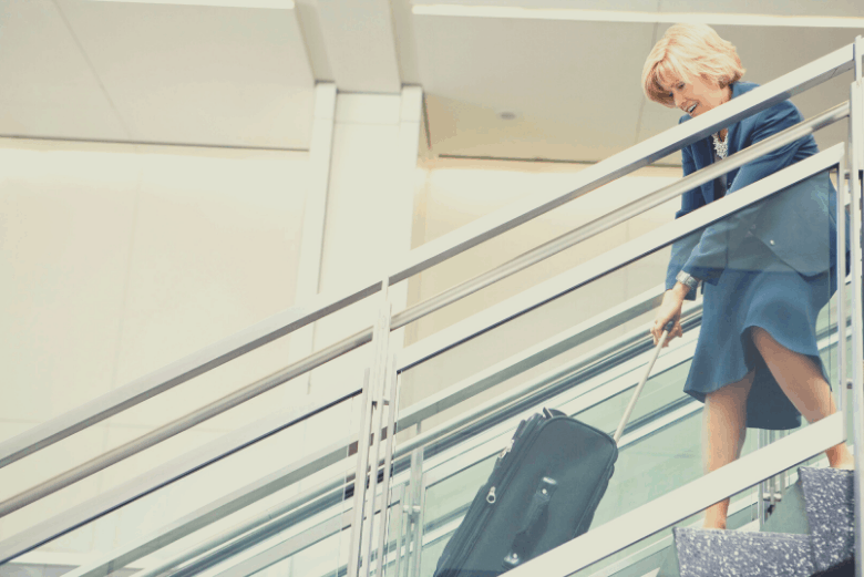 Woman dragging suitcase up stairs