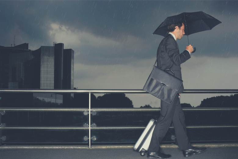 Man walking in rain with suitcase