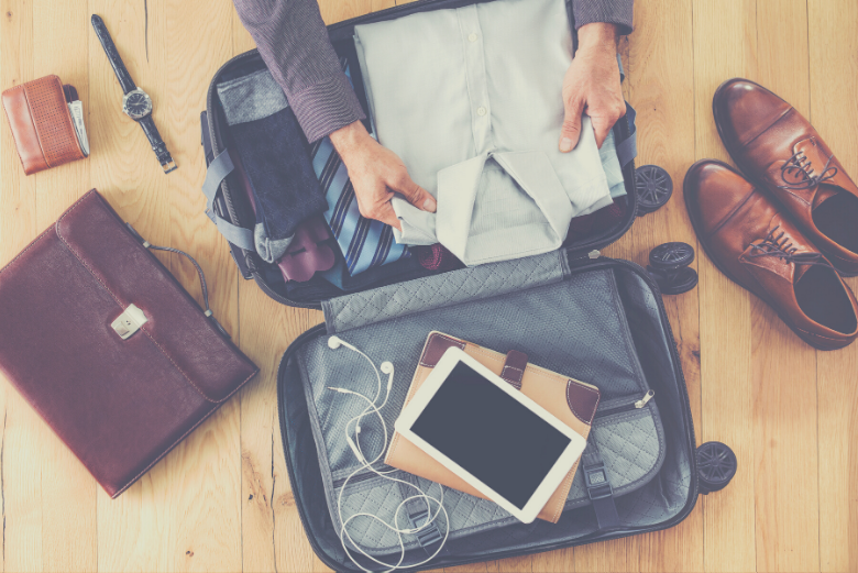 Person packing shirt into open suitcase