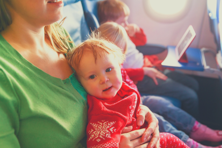 baby sitting on mother's lap on airplane