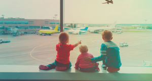 young kids at airport looking out at airplane